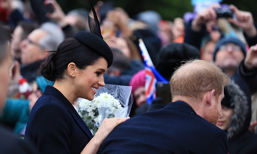 Meghan sweetly rested a hand on Prince Harry's shoulder as they chatted with fans outside the Sandringham church. 