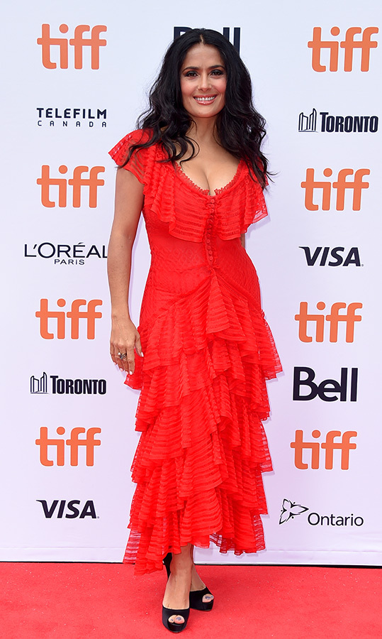 "<a href=""/tags/0/salma-hayek/"">Salma Hayek</a>, 52, brought the heat to the premiere of <em>The Hummingbird Project</em> in Toronto. The Spanish actress dazzled in a ruffled red gown with a buttoned torso and black heels, letting her gorgeous brunette locks fall in soft waves.