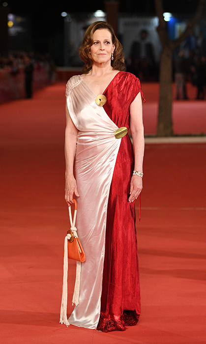 "<a href=""/tags/0/sigourney-weaver/"">Sigourney Weaver</a>, 69, stunned in a draped two-tone gown paired with a unique orange rope bag and gorgeous golden accessories while on the red carpet at the Rome Film Fest back in October.