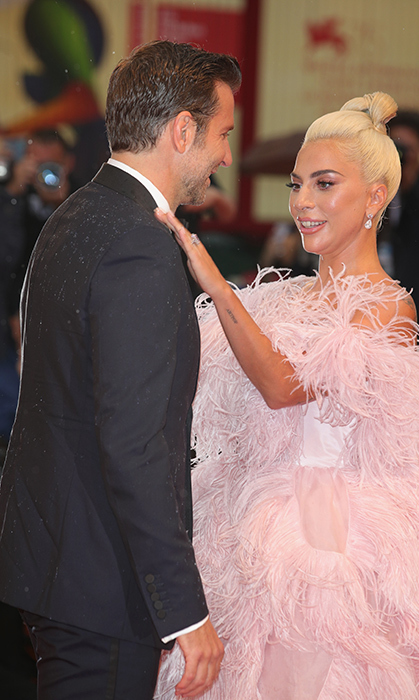 "The ""Poker Face"" singer helped out her friend by brushing off his tuxedo for the onslaught of photos at the Italian film festival. Too sweet!