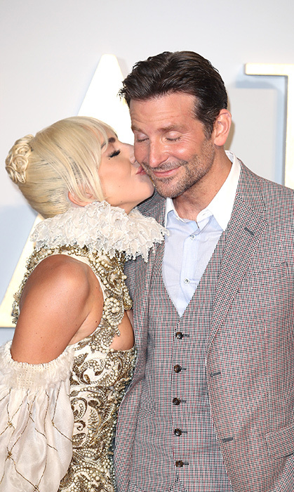 Smooch! Lady Gaga planted a cheeky kiss on Bradley's face at the UK premiere of their film. As always, no stone goes unturned when it comes to the singer's sense of style – this time, she wore a very Victorian look envisioned by fashion house Alexander McQueen. 
