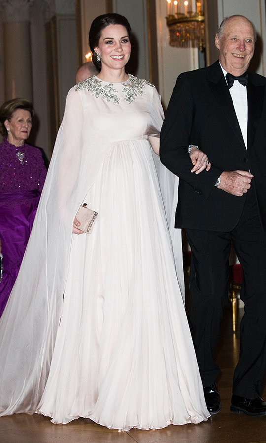 Pregnant Kate was the belle of the ball while on tour in Norway in 2018, dazzling in a caped, pale pink Alexander McQueen gown with silver embellishments while enjoying a state dinner at the Royal Palace in Oslo. She carried a pretty, jewel encrusted Jimmy Choo Clutch and wore the Queen's diamond drop earrings and bracelet that was a wedding gift from Prince Philip.