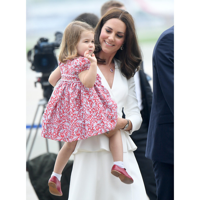 Princess Charlotte gave a royal wave as she arrived on her second tour with her parents and brother to Warsaw, Poland in July 2017. Duchess Kate looked obviously smitten with her adorable daughter, who wore her uncle Prince Harry's red shoes to match her dress.
