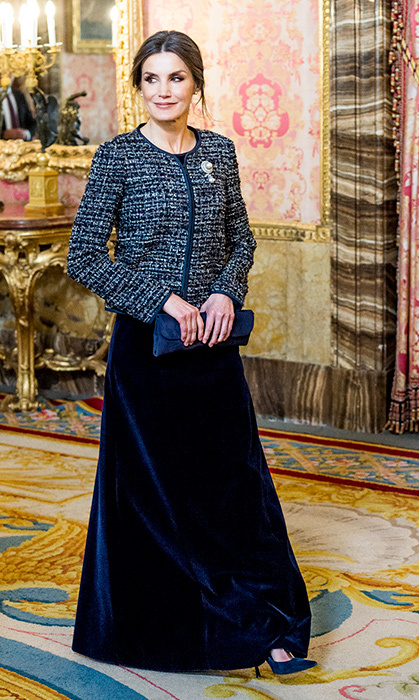 We can't get enough of this velvet glam! The Queen of Spain joined her husband for their first public engagement of the New Year on Jan. 6. Their majesties attended the traditional celebration of the Pascua Militar, for which Letizia stunned in a midnight blue velvet gown, keeping her arms warm in a navy Emporio Armani metallic-tweed jacket. She carried a slim navy blue clutch, which perfectly matched the navy pumps peeking out from under her dress.