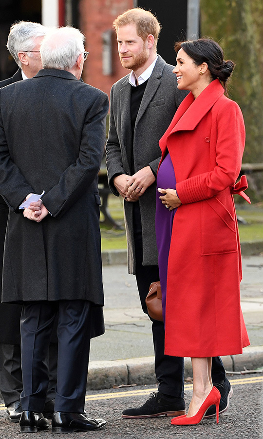 The royal mom-to-be protectively cradled her growing bump.