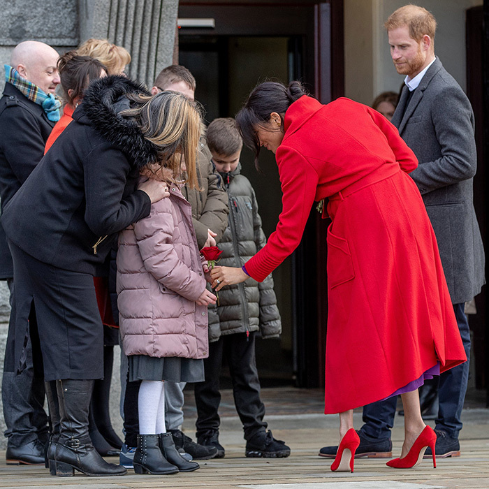 The stunning Duchess of Sussex graciously took the time to meet a trio of little kids outside the building.