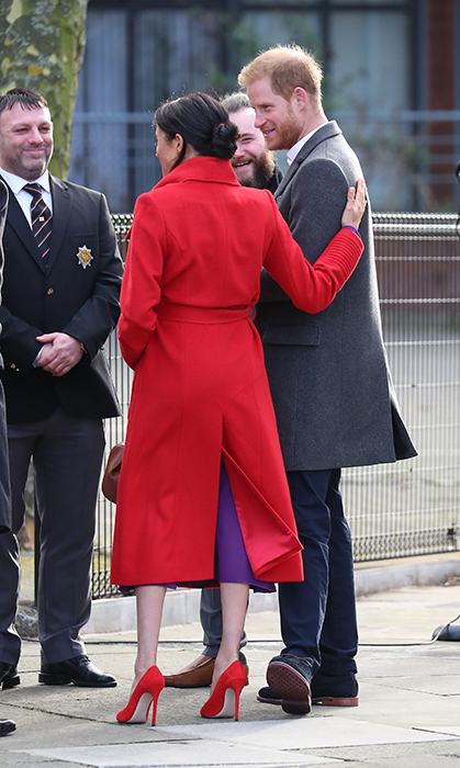 Meghan and Harry chatted with officials just after arriving. She lovingly rested a hand on her husband's back.