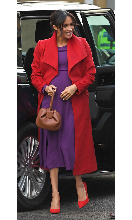 Duchess Meghan, who's currently six months pregnant, absolutely stunned in a bold cherry red coat by Canadian label Sentaler. She paired the look with Babaton for Aritzia's beautiful purple 'Maxwell' dress, anchoring the ensemble with crimson Stuart Weitzman pumps and her brown Gabriela Hearts 'Nina' bag.