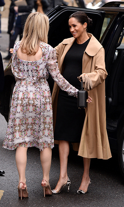 Meghan paired a maternity dress with an Oscar de la Renta swing coat at Smart Works.