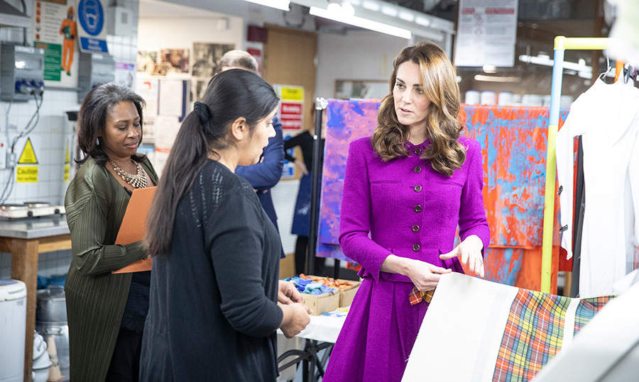 The brightly hued royal checked out some fabrics, chatting intently with one of the workers.
