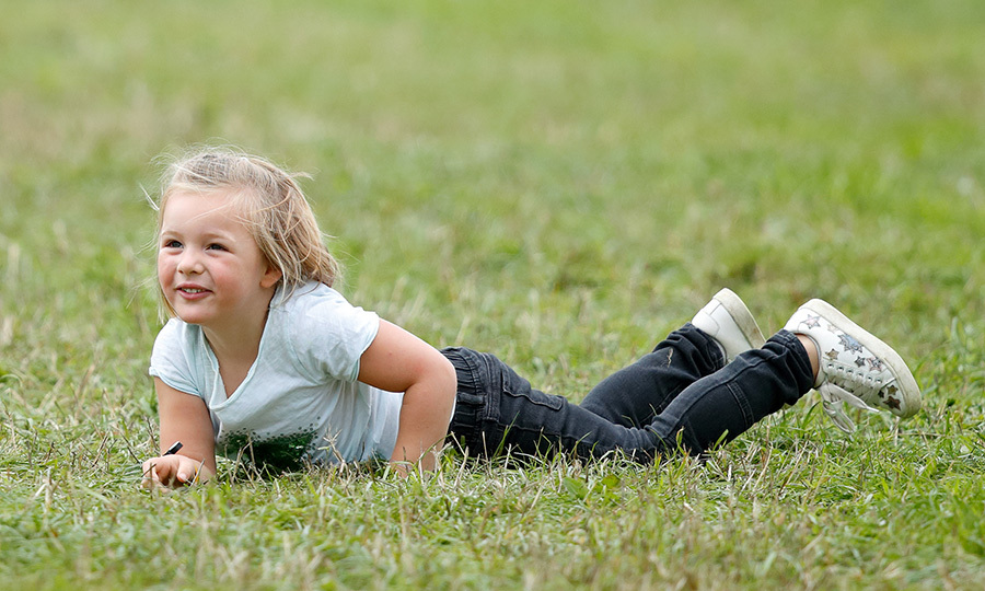 The spritely young royal had a blast playing with friends in the grass.