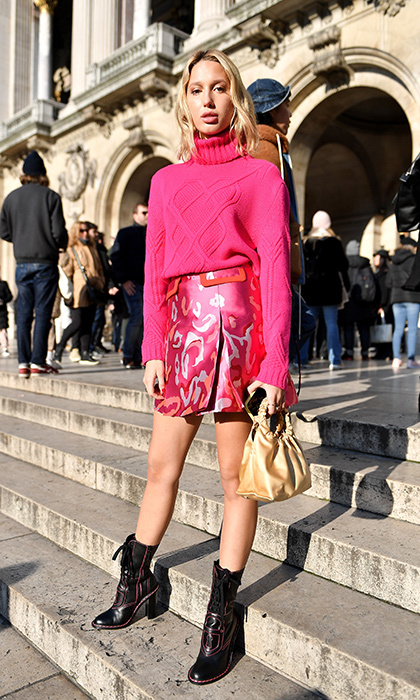 For her first look of fashion week on Jan. 21, Princess Olympia brought some major colour to the Schiaparelli show in Paris! The Grecian princess dazzled in a bright pink turtleneck sweater and a satin mini skirt, and anchored the look with chic black heeled booties.
