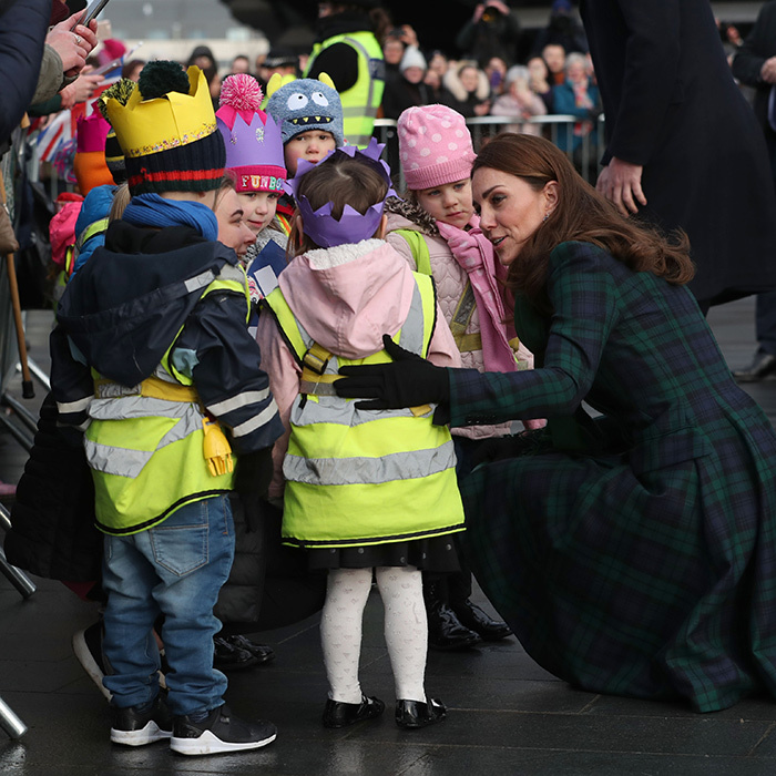 The mother of three had a sweet moment with a gaggle of kids waiting to greet her.