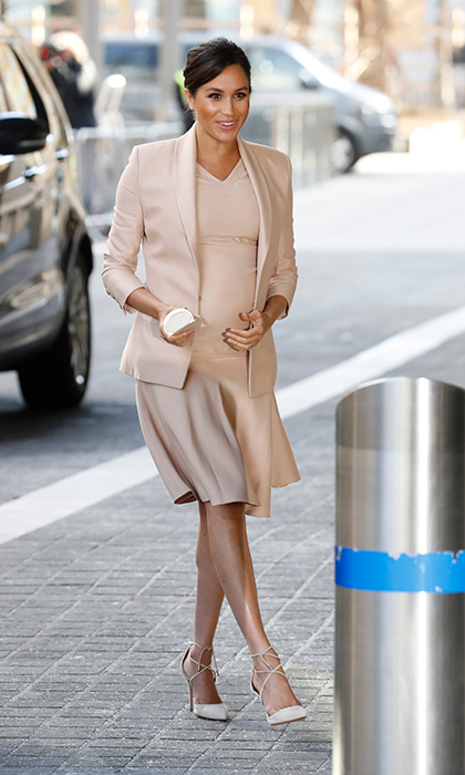 Duchess Meghan – who's due in the spring – dazzled in a cream Brandon Maxwell V-neck dress and blazer. She accessorized with a Carolina Herrera 'Insignia' clutch and her Aquazzura pumps, which she wore when she announced her engagement to Prince Harry on Nov. 27, 2017.