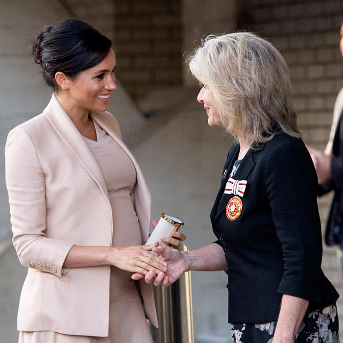 Meghan looked happy as ever to be greeted by Rosi Prescott of The National Theatre.