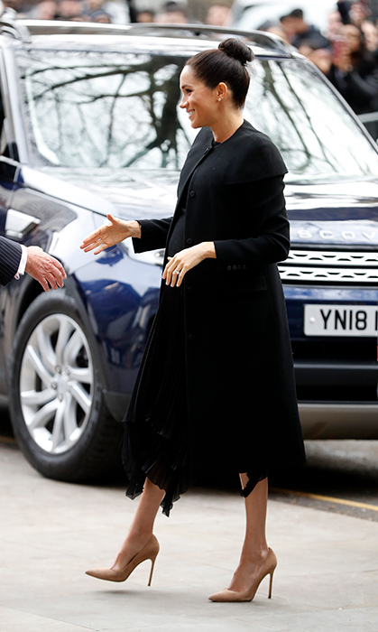 "The pregnant duchess looked no further than her wedding gown designer Givenchy, recycling the dark coat by the fashion house which she wore <a href=""https://ca.hellomagazine.com/royalty/02018111148540/meghan-markle-kate-middleton-the-queen-remembrance-sunday-cenotaph/1""><strong>for her first Remembrance Sunday</strong></a> service as a royal. She appeared to be wearing a pleated black skirt and black top underneath the piece, anchoring the look with a pair of beige suede heels.