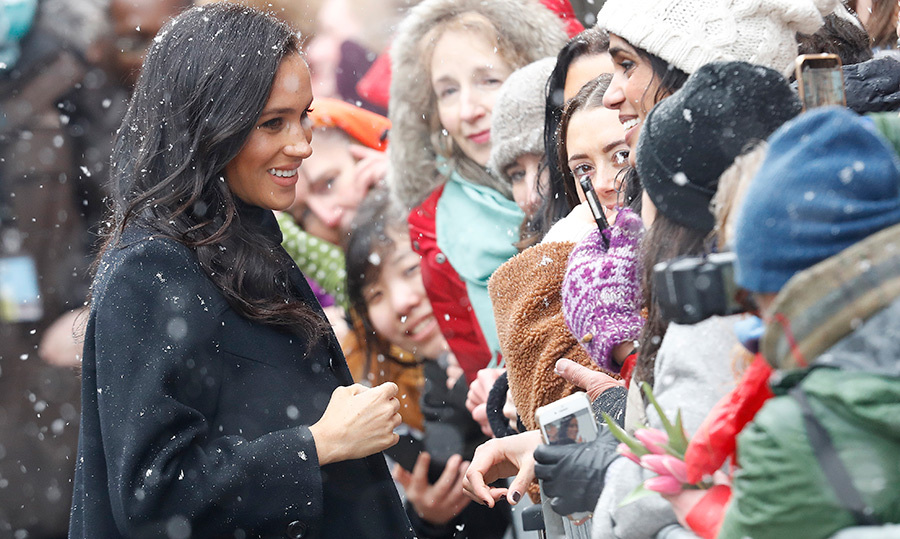 After being welcomed, the two headed over for a walkabout to greet some of the people who'd been waiting for them. Meghan showed off her winning personality by chatting with some eager young women waiting to see her.
