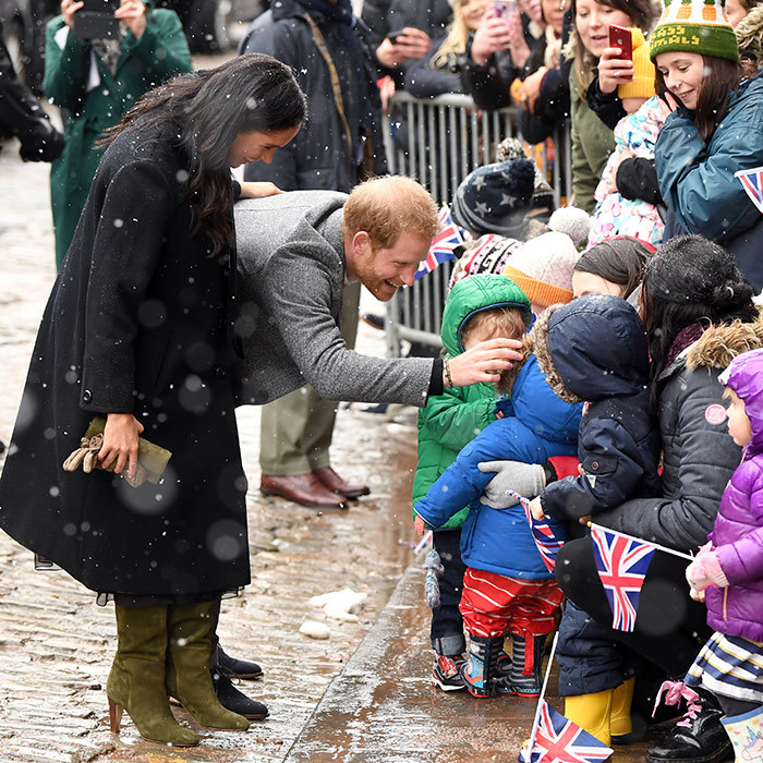 What's a royal walkabout without some cute kids? The parents-to-be adorably chatted with a gaggle of children outside of the Bristol Old Vic theatre – and Prince Harry even fixed one of their hoods!