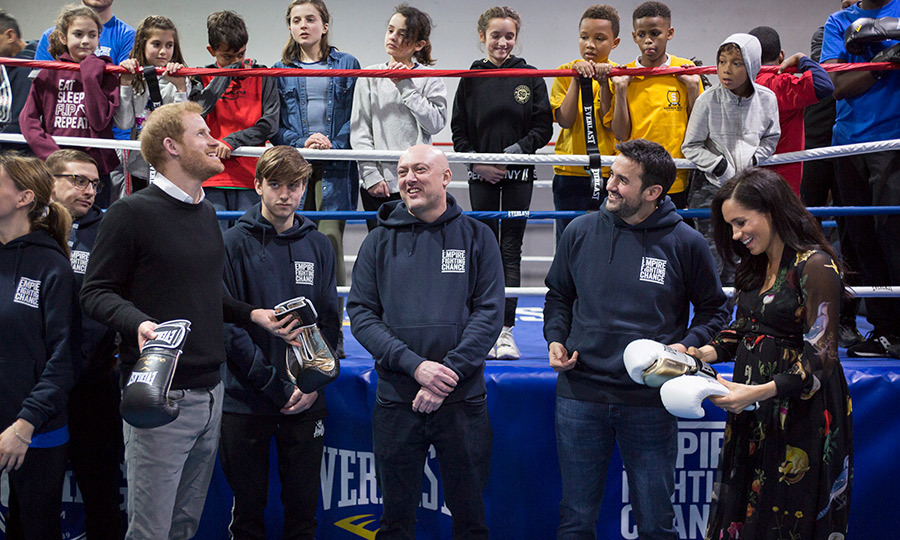 While stopping by the city's Empire Fighting Chance – a gym that supports local youth through the sport of boxing – Meghan and Harry got a kick out of their matching boxing glove gifts!