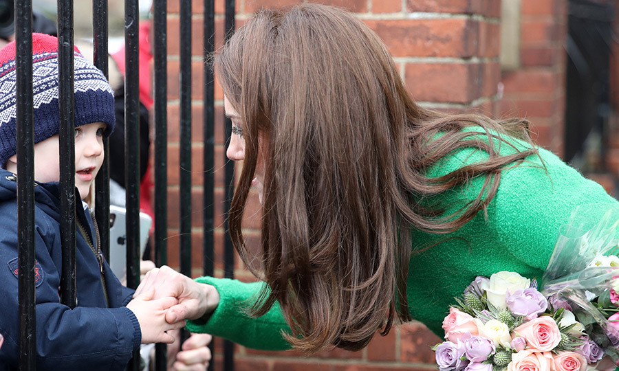 Showing off her big heart, the duchess clasped hands through a fence with an adorable little one.
