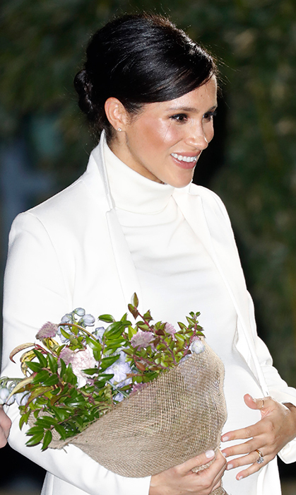 Fashioning her hair up in a sleek bun, the 37-year-old accessorized with a pair of green suede pumps and a small matching clutch to hold her necessities. Meghan amped up the glam when it came to her beauty look, taking her natural glow to a whole new level with added bronzer, highlight, a smoky eye and an overall dewy finish to her skin.