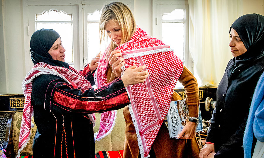 Máxima tried on a beautiful red-and-white scarf while visiting a guesthouse that gets support from Microfund for Women.