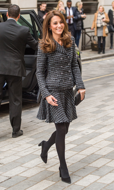 Wearing a silhouette she's loved as of late, the Duchess Kate paired her skirt suit with opaque grey tights, anchoring the ensemble with simple suede black pumps, for a mental health conference in London on Feb. 13.