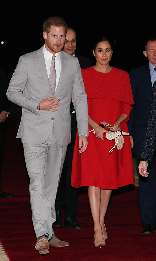 The Duchess of Sussex touched down in Morocco with her husband on Feb. 23, 2019 looking every inch the fashion-forward royal she is! She was radiant in a red bespoke <strong><a href=/tags/0/valentino>Valentino</a></strong> dress, designed based on a 2013 vintage-inspired collection by the fashion house. The pregnant duchess fashioned her raven locks in a chic and sleek bun, accessorizing her ensemble with a pair of beige gloves and a matching clutch, VRing Smooth Calfskin Crossbody Bag in pink by Valentino. She anchored the look with a bespoke pair of <strong>Rockstud</strong> pumps by the label, with the studs removed.