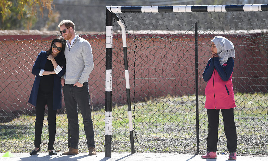 Harry and Meghan shared a sweet moment while on the soccer field. The duchess leaned into her husband.