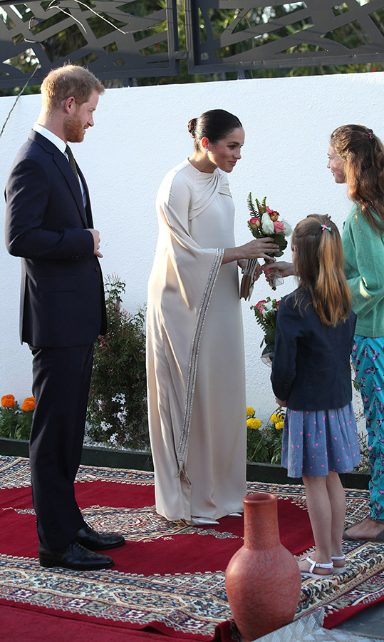 The duchess received a gorgeous bouquet of flowers from two sweet girls who were greeting the two at the reception.