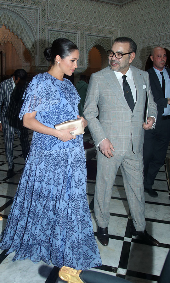 For their final engagement in Morocco, the Duchess of Sussex wowed in a gorgeous, floor-length print dress by Carolina Herrera – one of her favourite designers. She paired the look with nude pumps and her small satin Dior clutch, fashioning her hair up in a sleek bun to show off her Cartier earrings. Her beauty look was a bit more colourful than her classic bronzed cheek – she used a gorgeous coral blush.