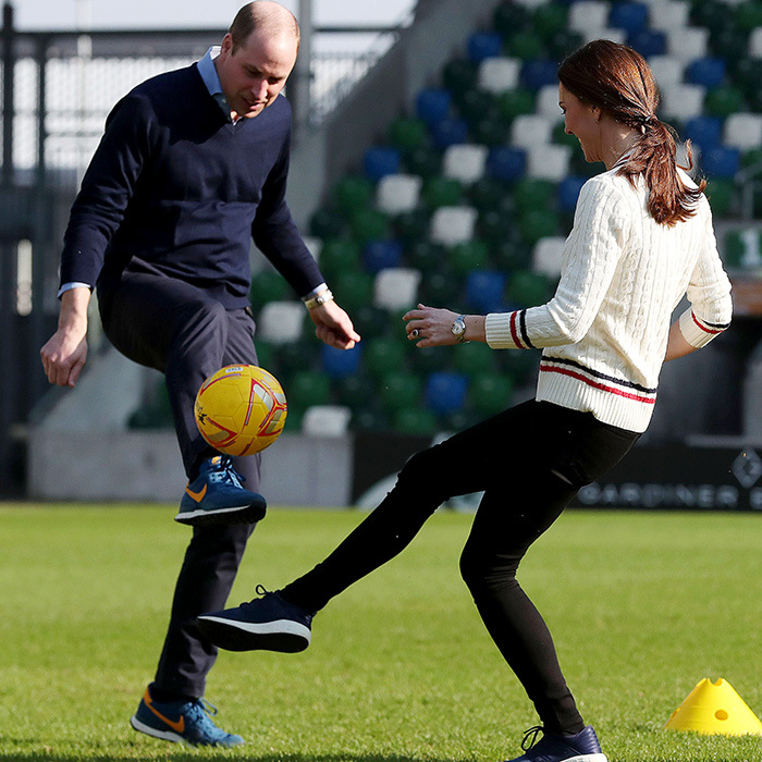 The duke and duchess playfully fought over a soccer ball.