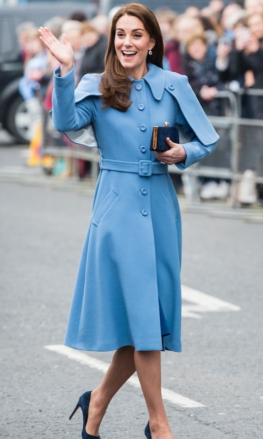 Duchess Kate turned heads in a stunning brand new cornflower blue Mulberry cape-style coat. Underneath, she wore a royal blue dress, anchoring the ensemble with navy blue suede pumps and a small clutch to match. She also wore a pair of beautiful drop earrings.