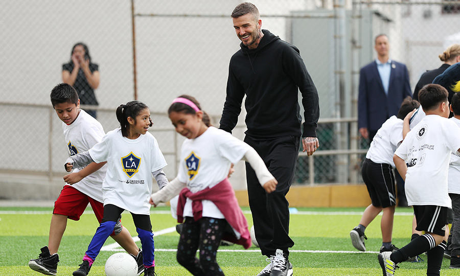So sweet! Former soccer player David Beckham helped some young players with their soccer drills at a refurbished community soccer field at The Salvation Army Red Shield Youth & Community Center on March 1 in Los Angeles.