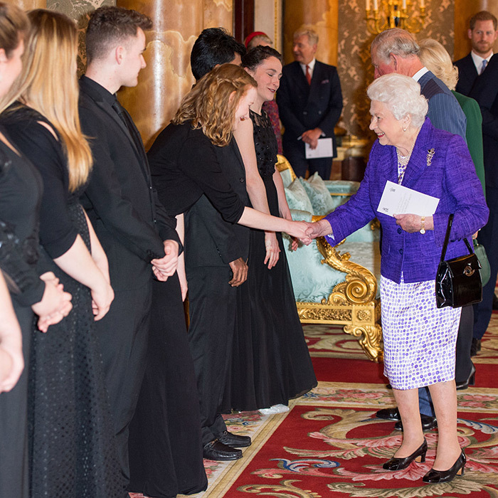 "For the investiture ceremony, <strong><a href=""https://ca.hellomagazine.com/tags/0/queen-elizabeth"">Queen Elizabeth II</a></strong> dazzled in a purple jacket and a purple-and-white dress. She paired the look with black pumps and one of her favourite handbags.
