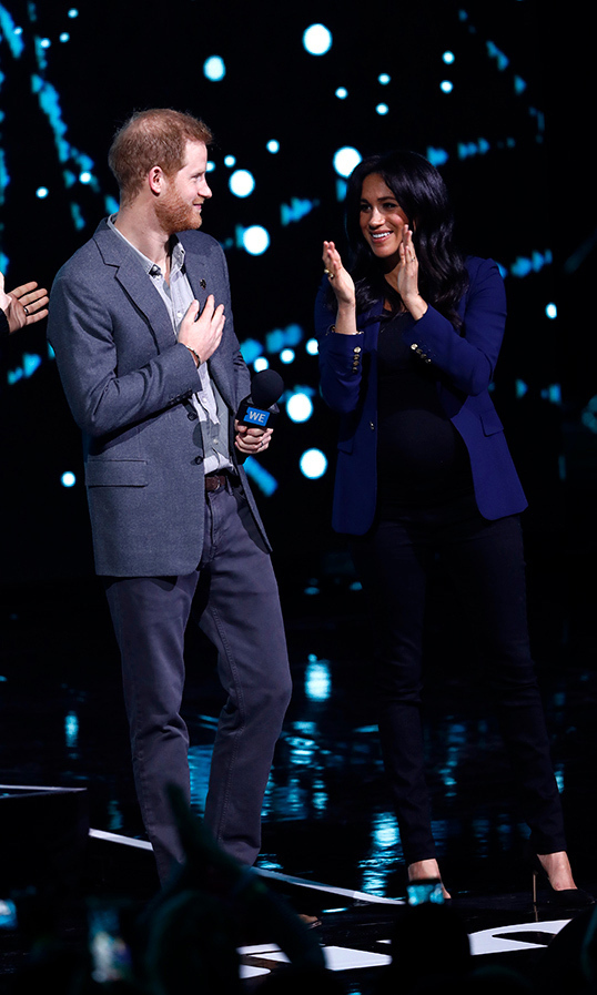 "Duchess Meghan surprised royal watchers when she joined Prince Harry on the WE Day stage on March 6! Meghan let her raven hair down and donned a pair of black maternity Rag & Bone jeans, a black shirt and a chic blazer. Anchoring the look with her black Monolo Blahnik pumps, she accessorized with her Pippa Small bangles and a special gift from one of her baby shower goers – her gold ""mummy"" necklace by Jennifer Meyer.