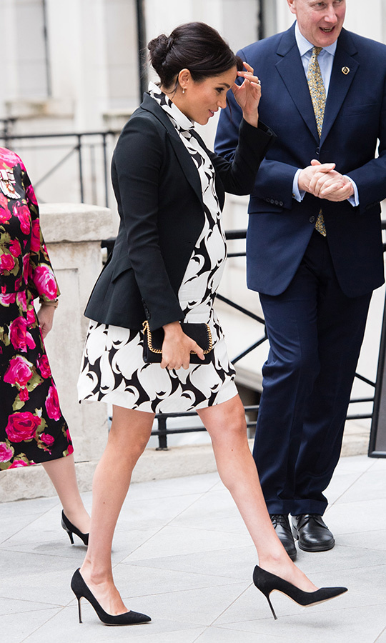 Duchess Meghan stepped out in London to celebrate a very important day to her – International Women's Day on March 8! The 37-year-old wowed in a sweet mod mini dress from affordable British brand REISS. She paired the black-and-white number with a blazer by Alexander McQueen (one of Duchess Kate's favourite designers!), anchoring the look with her black suede Manolo Blahnik BB pumps and her favourite Stella McCartney clutch – the Shaggy Deer Faux Leather Crossbody. Of particular note was Meghan's brooch, fixed with the symbol for the Queen's Commonwealth Trust.