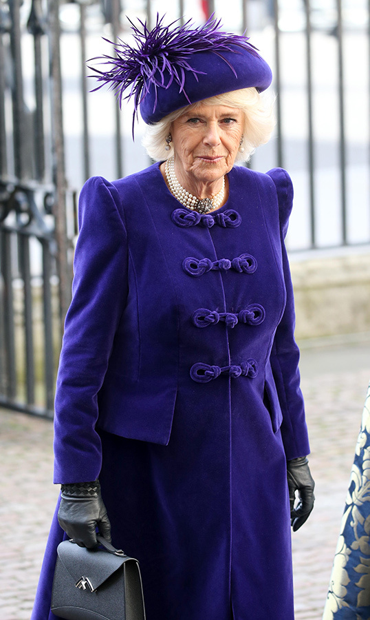 Camilla, Duchess of Cornwall, matched the Queen in a beautiful purple velvet coat and a matching feathered hat. She kept her hands warm in black leather gloves and carried a black envelope purse. Around her neck, the duchess wore a four-strand pearl necklace.