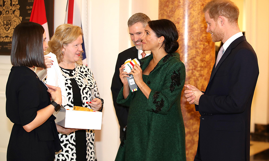 Duchess Meghan appeared particularly touched by the baby-sized Hudson's Bay mittens presented to her by Janice Charette, Canadian Commissioner to the United Kingdom during the event. We can't wait to see Baby Sussex wearing them! 
