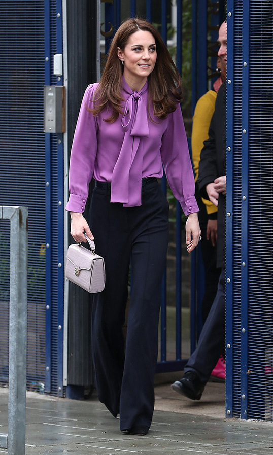 "<strong><a href=""https://ca.hellomagazine.com/tags/0/kate-middleton"">Duchess Kate</a></strong> arrived at the Henry Fawcett Children's Centre with her best fashion foot forward! The 37-year-old brought some colour to the otherwise cloudy day, dazzling in a pink-purple pussybow blouse by one of her go-to luxury designers and black wide-leg trousers by British brand Jigsaw. As for accessories, Kate carried a small patent handbag by Aspinal, anchoring the ensemble with black suede pumps.
