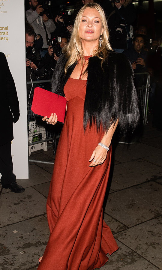 Supermodel Kate Moss dazzled in a burnt orange gown, accessorizing with a black fur shawl.