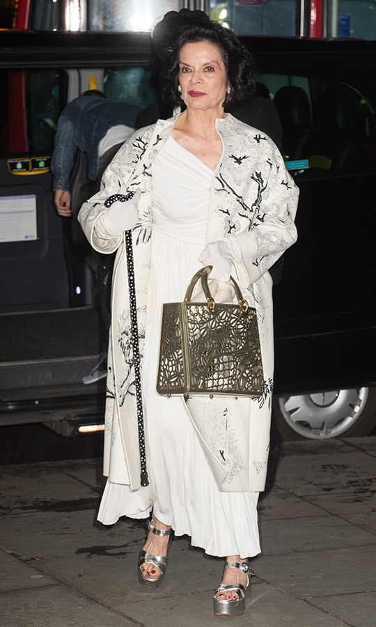 Bianca Jagger arrived with her best fashion foot forward, dazzling in a white dress paired with metallic platform sandals and a crocodile-print purse.
