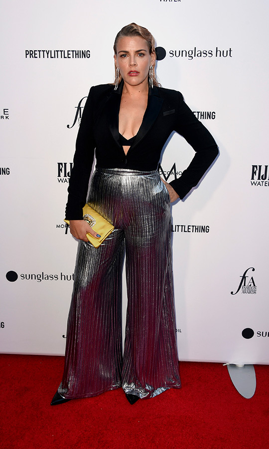 <strong>Busy Philipps</strong> wore a unique look that included a black top with a plunging neckline and metallic pants. She accessorized with a yellow clutch. 
