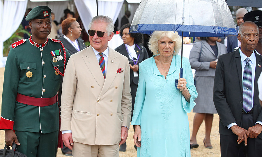 It was a bit of a rainy day when the royal couple arrived, so Camilla pulled out another umbrella. She's already made good use of another to protect her from the sun during the couple's Caribbean trip. Charles decided to keep his sunglasses on, and looked debonnaire in tan! 