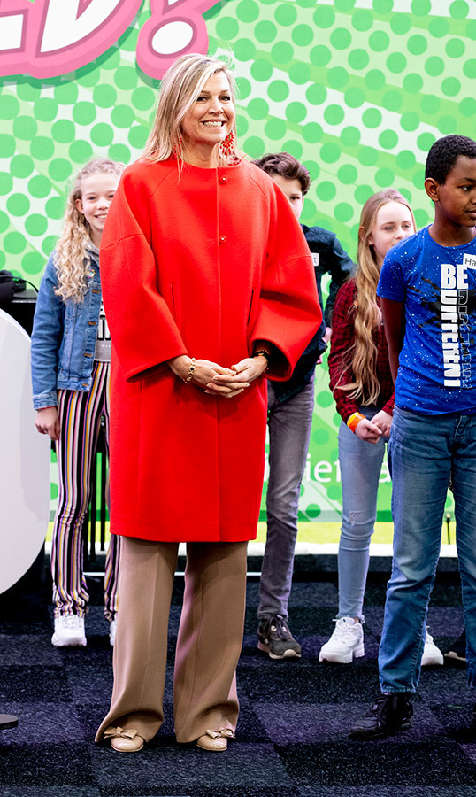 March 25 marked Queen Maxima's bright appearance at the 'Are you a hero with your money' even in The Netherlands. She dazzled in a gorgeous vibrant red coat, paired with beige wide-leg trousers and matching pumps. Of course, she didn't forget her winning smile!