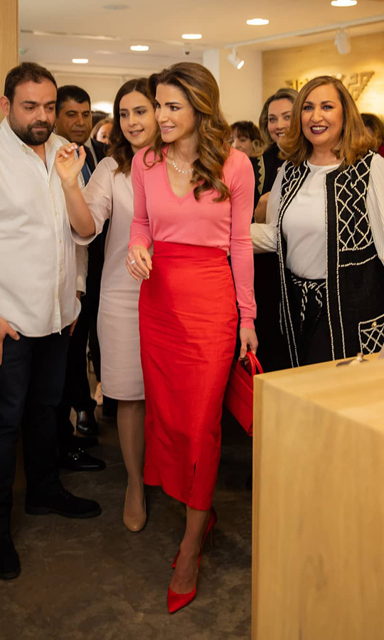 "<a href=""https://ca.hellomagazine.com/tags/0/queen-rania""><strong>Queen Rania</a></strong> made quite the fashion statement during a visit to the Jordan River Foundation's annual handicrafts exhibition on April 2. Glamorous as ever, the Jordanian royal paired a pink v-neck sweater with an orange pencil skirt, anchoring the ensemble with orange satin pumps and carrying a darling handbag of the same colour. She fashioned her hair in voluminous waves, keeping her beauty look simple and refined.