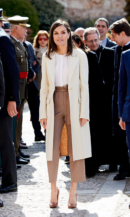 "We know another royal who'd love that coat! On April 11, <a href=""https://ca.hellomagazine.com/tags/0/queen-letizia""><strong>Queen Letizia</a></strong> dazzled in a cream and camel two-tone wrap coat (that Duchess Meghan would die for) for a visit to the <em>Agneli</em> exhibit in Burgos, Spain. She paired the statement piece with her Hugo Boss 'Banora' silk blouse and tan 'Alantia' trousers by the same brand. She anchored the look with block heel pumps by Hugo Boss, too.