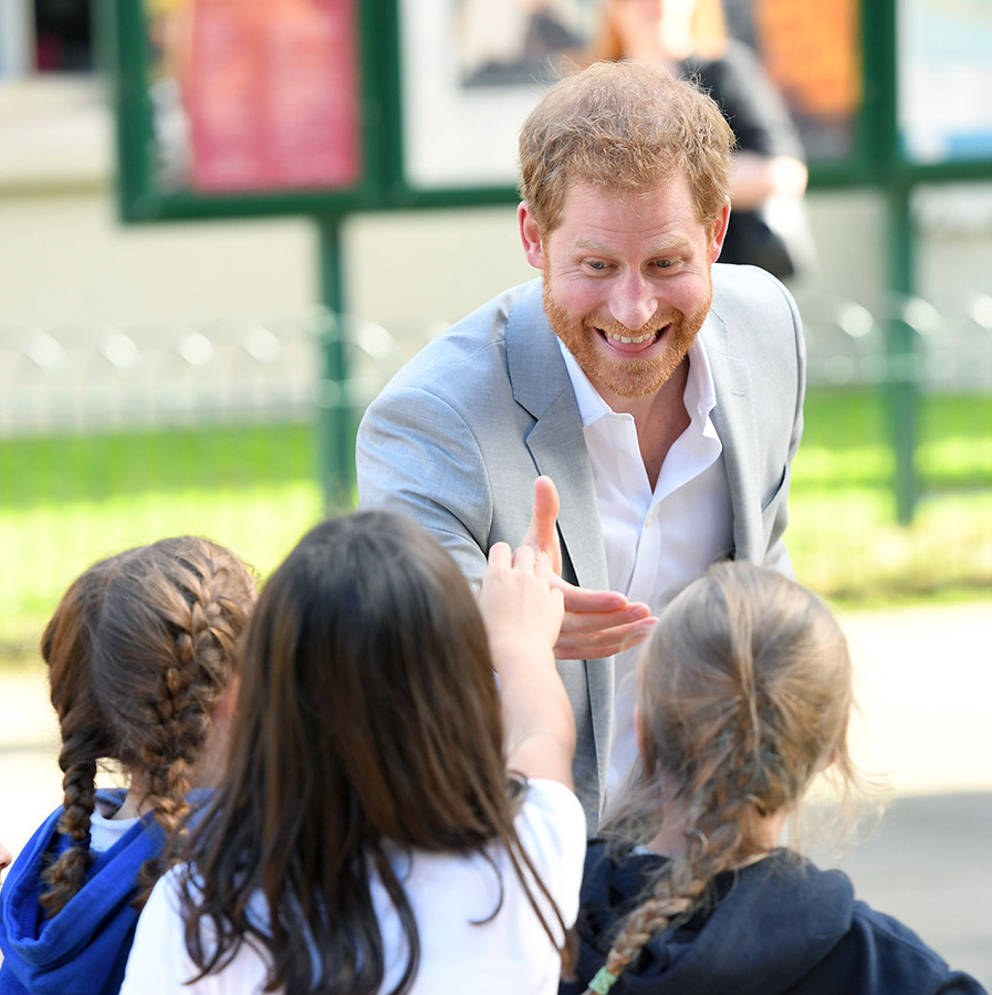 Clearly full of charm, the Duke of Sussex goofed around with a trio of kids, giving them a few handshakes.
