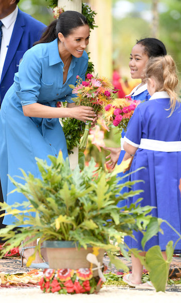 Here's mom-to-be Meghan, receiving a beautiful bouquet from a pair of sweet little girls at another event.