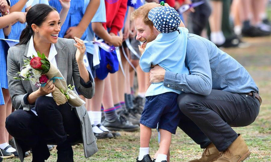 Meghan got a case of the giggles as future father Harry got a big hug from this adorable little fan!